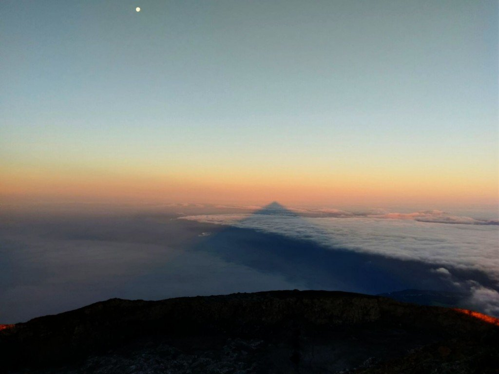 Photograph by John Plum. Pico Volcano Sunset and shadow of Pico Volcano on the clouds