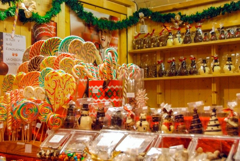 Wooden kiosk with heart shaped candies, lollypops and other treats and gifts for Christmas in Ljubljana, Slovenia - Global Storybook