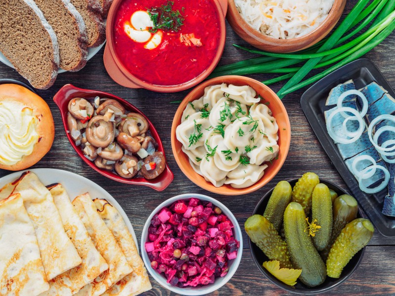 Wooden table with dishes of russian cuisine - borscht, pelmeni, herring, marinated mushrooms, salted cucumbers, vinaigrette, sauerkraut, rye bread, pancakes, cheese pastry, Russia - Global Storybook